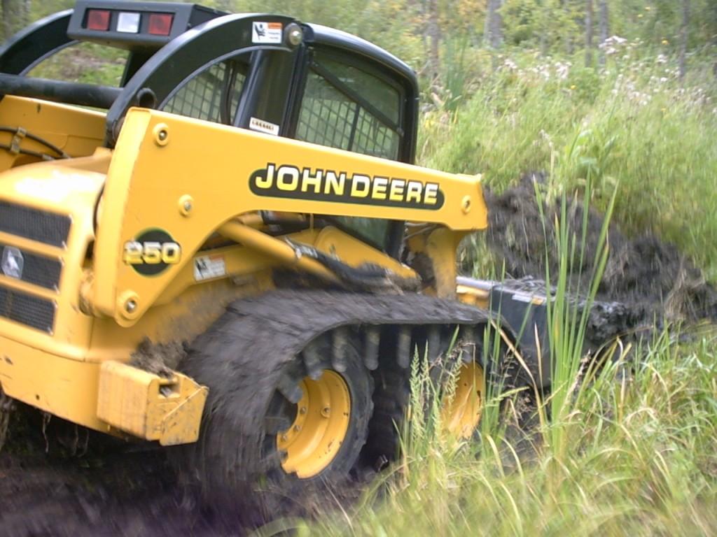 skid steer tracks in use on John Deere
