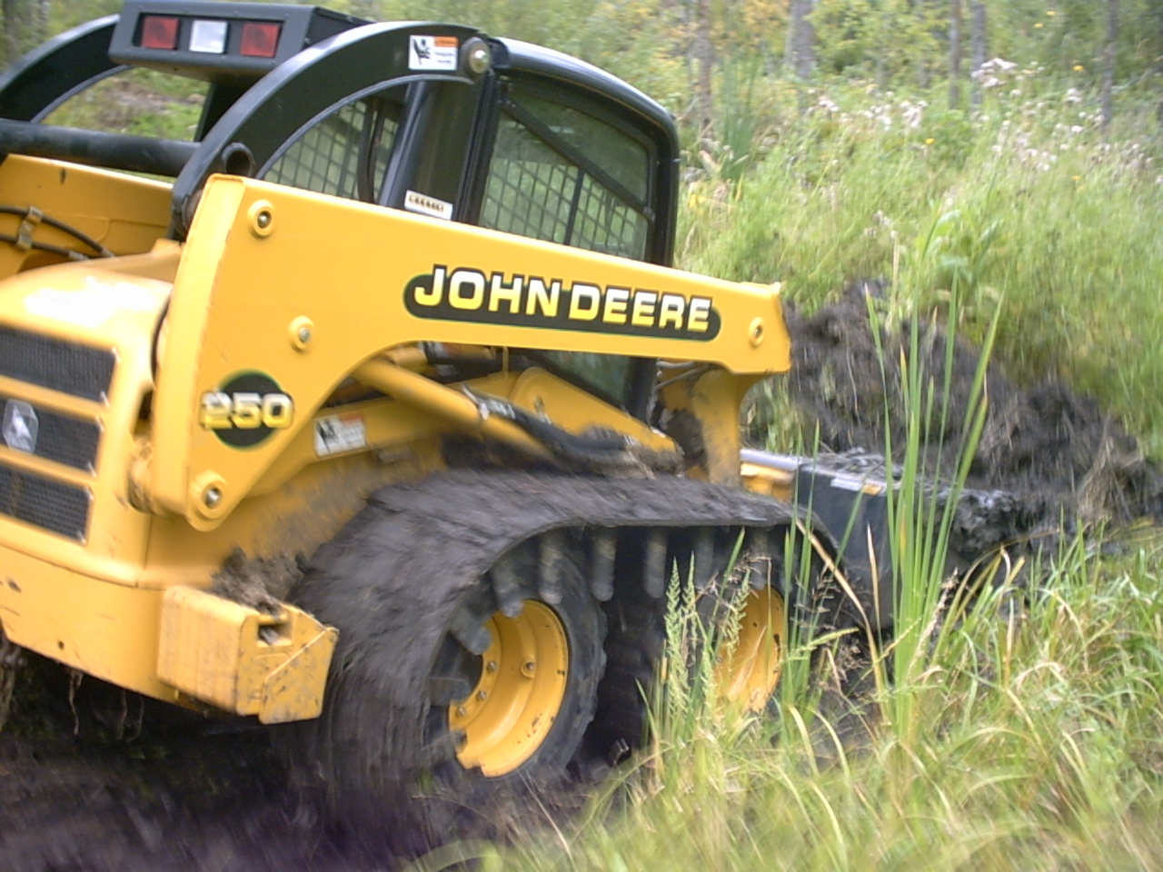 skid steer tracks in use on John Deere
